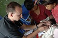 US Navy 080818-N-3595W-150 U.S. Air Force Capt. Heath Wright, a pediatrician currently embarked aboard the amphibious assault ship USS Kearsarge (LHD 3), performs a medical examination on an infant at a medical site.jpg