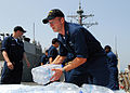 US Navy 080824-N-4044H-095 Cryptologic Technician 1st Class Jed Morris stacks bottles of water aboard the guided-missile destroyer USS McFaul (DDG 74), which will be included in the humanitarian supplies for the people of Georg.jpg