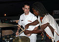 US Navy 090227-N-1655H-352 Musician 2nd Class Ross Hartig, assigned to the Commander, U.S. Naval Forces Europe Band, and a Ghanaian drummer compare notes during a reception for Ghanaian distinguished visitors aboard the amphibi.jpg