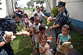 US Navy 090728-A-1839I-041 Sailors assigned to the amphibious dock landing ship USS Oak Hill (LSD 51) hand out teddy bears to local children at Marambaia Island, Brazil. Oak Hill is participating in Southern Partnership Station.jpg