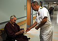 US Navy 090914-N-9824T-065 Rear Adm. Scott Weikert, deputy commander of 1st Naval Construction Division, gives a Navy mug and lanyard to a D-Day veteran at Lebanon VA Medical Center.jpg