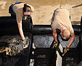 US Navy 110721-N-WW084-057 Seabees use putty knives to scrape off excess asphalt from a paving machine.jpg