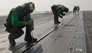 US Navy 120108-N-OY799-117 Sailors replace catapult buttons on the flight deck of the Nimitz-class aircraft carrier USS John C. Stennis (CVN 74).jpg