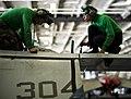 US Navy 120116-N-BT887-050 A Sailor checks an electric drive for a folding wing on an F-A-18C Hornet.jpg