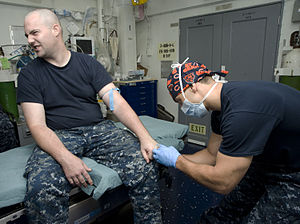 US Navy 120120-N-JN664-018 Hospital Corpsman 1st Class Albert Aguilar inserts an intravenous tube into the arm of Mass Communication Specialist 2nd.jpg
