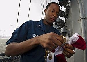 US Navy 120124-N-FI736-009 Quartermaster 3rd Class Anton Allen prepares to hoist the national ensign aboard the aircraft carrier USS Enterprise (CV.jpg