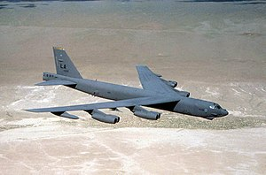 Aerial top/side view of gray B-52 overflying barren land.
