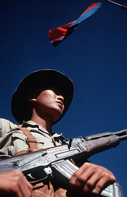 Viet Cong soldier stands beneath a Viet Cong flag carrying his AK-47 rifle. He was participating in the exchange of POWs by the International Commission of Control and Supervision in 1973 Viet Cong soldier DD-ST-99-04298.jpg