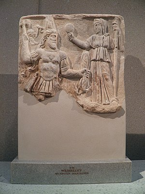 Jupiter Dolichenus - Votive relief to Jupiter Dolichenus (left, with double-axe and lightning bolt) and Juno Dolichena (right, with mirror and scepter). From Rome, 3rd-century.