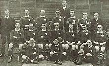 Несколько рядов игроков и официальных лиц, одетых в их игровую форму.