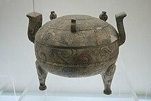 Photographie montrant une poterie de forme sphérique, supportée par 3 pieds (2 visibles uniquement) et ornée de deux poignées diamétralement opposées sur le haut de l'objet.