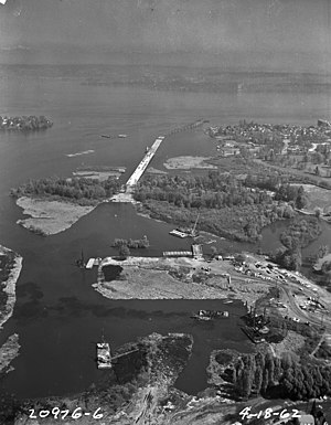 Evergreen Point Floating Bridge - Aerial view of the Evergreen Point Floating Bridge under construction, 1962. This shows the causeway extending from Foster Island in the Washington Park Arboretum roughly east to where Union Bay opens up into Lake Washington. Evergreen Point is across the lake.