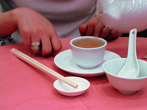 Yum cha - A tea-drinker tapping the table with her fingers to show gratitude to the member of the party who has filled her cup.