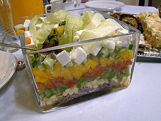 Feta - Vegetable salad with feta cheese (white blocks near top layer of salad).