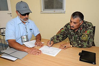 End user - NATO official and Afghan colonel going through end-user documentation to transfer control of barracks to the Afghan army in 2009