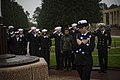 180408-N-JI086-312 - PO3 Kelly Carlson holds U.S. flag during a ceremony at the Normandy American Cemetery.jpg