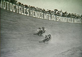 Thor (motorcycles) - Two people on motorized bicycles race on a board track in 1911