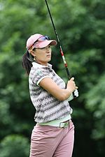 A dark-haired woman is wearing lavendar colored pants with a shirt that has colorful geometrical shapes on it with a lavendar hat and sunglasses on the bill of the cap and a graphite shafted golf club after a golf swing is up in the air