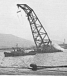 A large crane being towed by a boat in the water