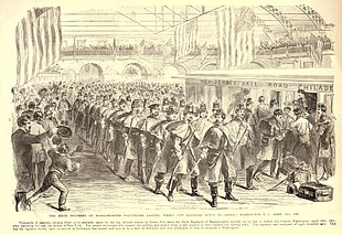 A black and white lithograph depicting a long column of soldiers at a large train station preparing to board a train