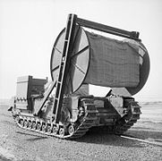 A tank with a large reel of matting carried in front of it