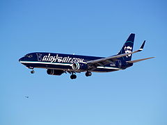 "Left side view of an Alaska Airlines 737-800 painted in a  primarily black livery, and says ""alaskaair.com"" on both sides. Aircraft is airborne."