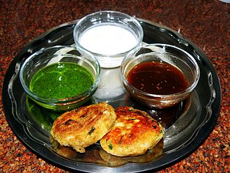 Croquette - Aloo tikki served with mint and tamarind sauce and dahi (yogurt) in India.