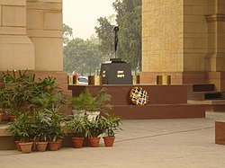 The tomb of the Unknown Soldier. The Amar Jawan Jyoti (the flame of the immortal warrior). A black marble cenotaph with a rifle crested by a helmet forms the main shrine.