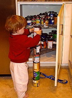 Young red-haired boy facing away from camera, stacking a seventh can atop a column of six food cans on the kitchen floor. An open pantry contains many more cans.