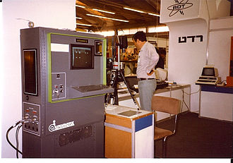 Machine vision - Early Automatix (now part of Omron) machine vision system Autovision II from 1983 being demonstrated at a trade show. Camera on tripod is pointing down at a light table to produce backlit image shown on screen, which is then subjected to blob extraction.