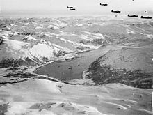 Black and white photograph of a group of aircraft flying in formation above a fjord surrounded by snow-covered mountains