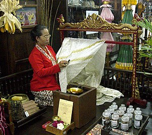 A Batik Tulis maker applying melted wax following pattern on fabric using canting, Yogyakarta, Indonesia.