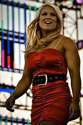 A blonde haired woman wearing a red santa hat and red dress with a black belt.