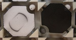Flip-disc display - Flip-disc display elements (close up). The disc rotates on the shaft that is carried in the two triangular posts. The magnet that powers the rotation can be seen embedded in the disc. Under the disc is the driving solenoid; when powered, a field is induced into the two posts, flipping the discs. Rotation stops when the disc hits the post.