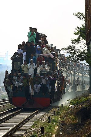 Train surfing - A crowded train with passengers riding on the outside in Bangladesh
