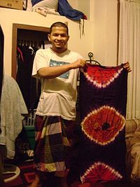 9b1f64c974 Bangladeshi actor Zubair Hasan from Sydney, Australia wearing a traditional lungi  and holding up a colorful lungi.