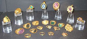22 gold and jewelled rings in a display case