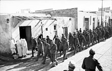 U.S. troops taken prisoner during the battle march through a Tunisian village
