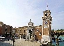 Fargebilde av en befestet port prydet med løver, til høyre et klokketårn