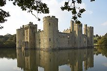 Photo of Bodiam Castle across the water, framed by oak leaves. The alternation of large round towers at the corners and square towers central to each face can be seen. Daylight visible through upper windows indicates that the roofs and inner structures are ruined.