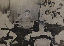 Un groupe de 6 hommes est assis à une table, l'un d'entre eux signe un document; ils sont observés par 3 hommes debout sur la gauche