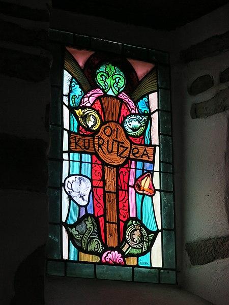 """Stained glass window """"Kurutzea"""" of the chapel of Saint Lawrence of Guermiette in Saint-Étienne-de-Baïgorry (Pyrénées-Atlantiques, France)."""
