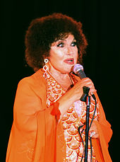 A woman wearing an orange dress and earrings, holding a microphone.