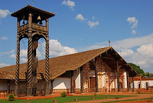 A wooden bell tower and a church in three-quarter view. The bell tower consists of a roof-covered platform supported by four columns with twisted fluting. Clocks are attached to the platform and a spiral staircase leads to it. The facade of the church is white and decorated with orange paintings. The church roof is rather large.