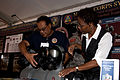 Corlis McClendon, right, project officer for Soft Wall Shelters, and Jeff Lizama, display manager for Combat Support Equipment, set up the gas mask display at the Modern Day Marine Military Exposition aboard 110929-M-BZ983-623.jpg