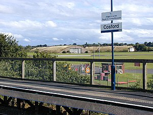 Cosford railway station - The pre-2012 station with wooden platforms. The aerodrome can be seen in the background.
