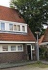 foto van Blok met 2 keukenwoningen, zo genoemd vanwege destijds nieuwe plaatsing van keuken aan de voorzijde, aan de zijkant een houten topgevel, bouwstijl Amsterdamse School, aansluitend op andere keukenwoningen in Tuindorp Nieuwendam