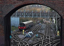 A view through a red-brick archway of a bridge. A complex of railway tracks interconnected with points is in the foreground with a train in the distance