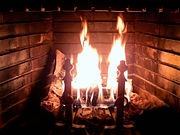 Wood-burning fireplace with burning log. Some other logs become dried and heated up around the fire  so that they will be burned better.