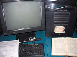"Black equipment on a teal blue desk. At left a monitor and at right a cube, both with small NeXT logos and in front a keyboard that says ""Propriete CERN"". Resting on the keyboard is a copy of ""Information Management: A Proposal,"" and to its right is a book, probably ""Enquire Within upon Everything"". A partly peeled off label on the cube says, ""This machine is a server. DO NOT POWER IT DOWN!!"""